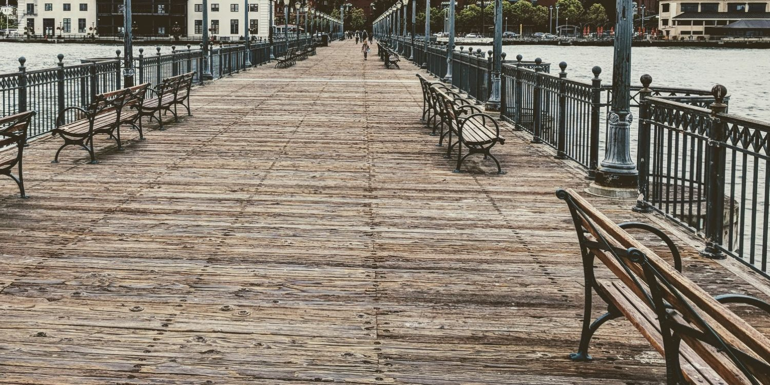 empty wooden benches on a long pier in San Francisco
