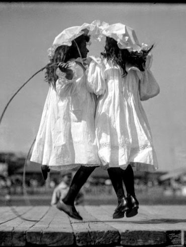two girls wearing white dresses are skipping rope