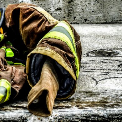 firefighter's suit crumpled on sidewalk