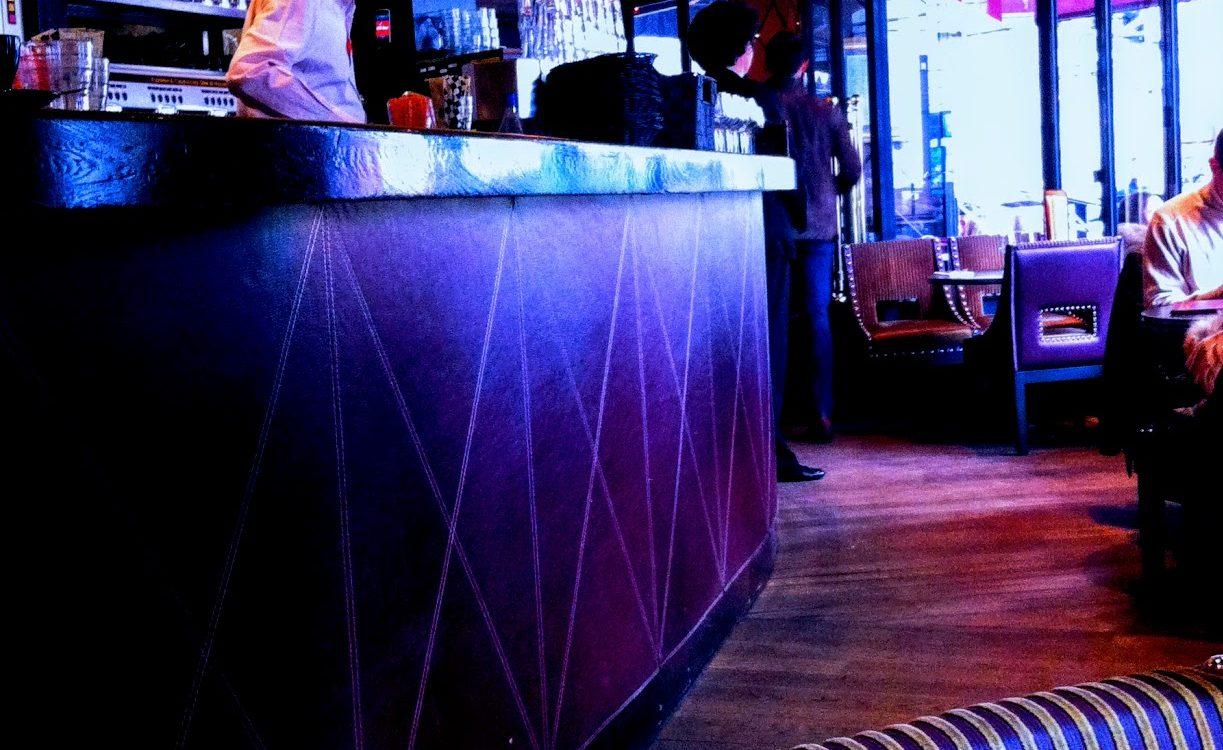 bartender behind a bar in a dark room