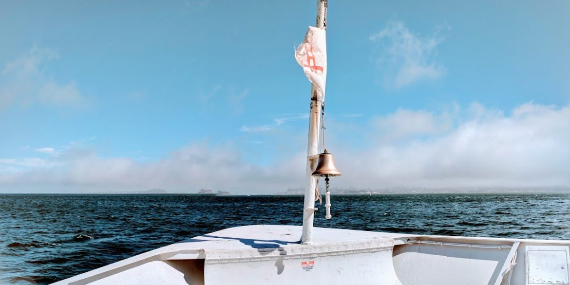 ripped flag flapping on bow of boat heading into open water