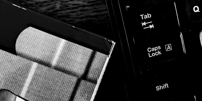 computer keyboard beside a box of bandaids