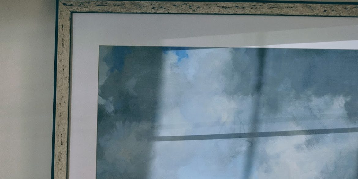 painting in frame shows blue sky and clouds