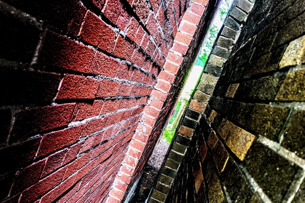red brick and brown brick walls of two adjoining houses
