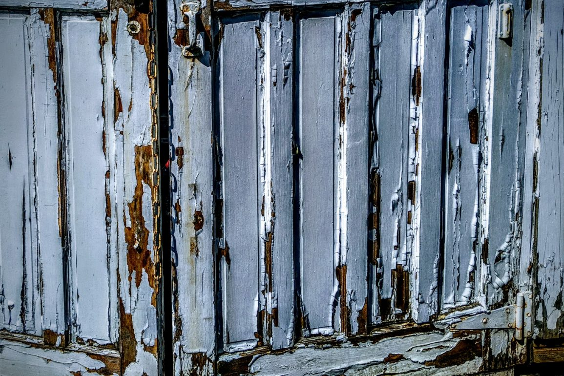 peeling paint on white wooden gate