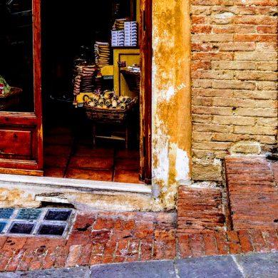 brick street in front of open shop doorway
