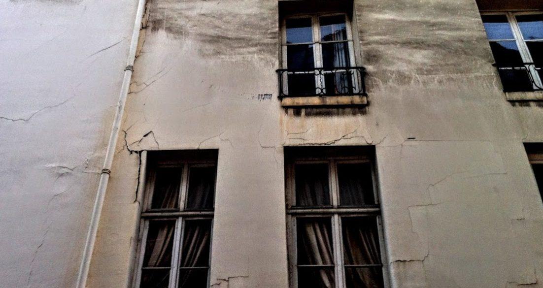 old Paris apartment building with dark windows