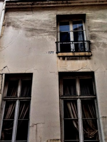 old Paris apartment building with dark windows