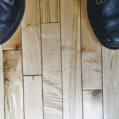 looking down at a man's shoes on hardwood floor