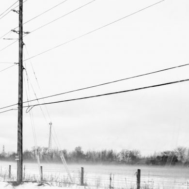telephone pole and wire fence in front of cold snowy field