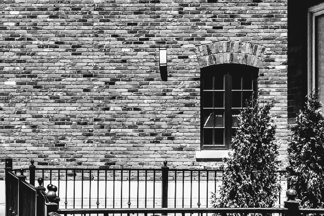 window in brick wall with black iron fence