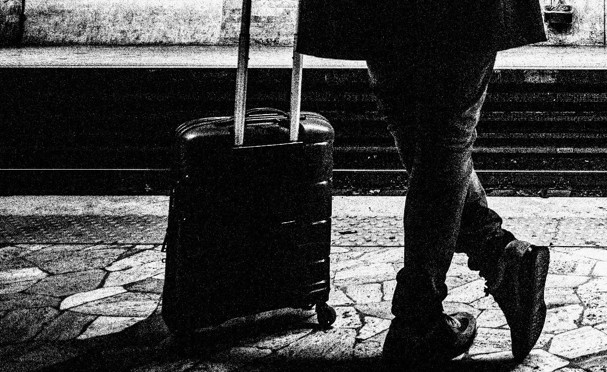 man waits on train platform with a roller suitcase