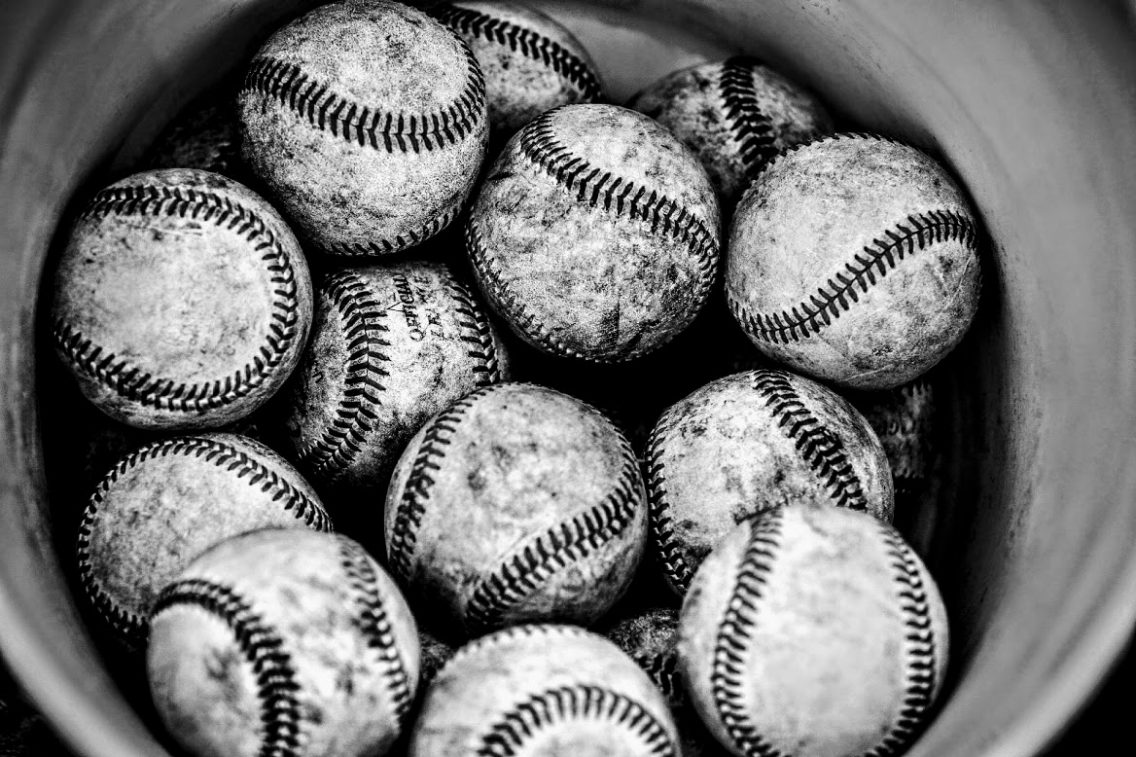 a dozen baseballs in a bucket