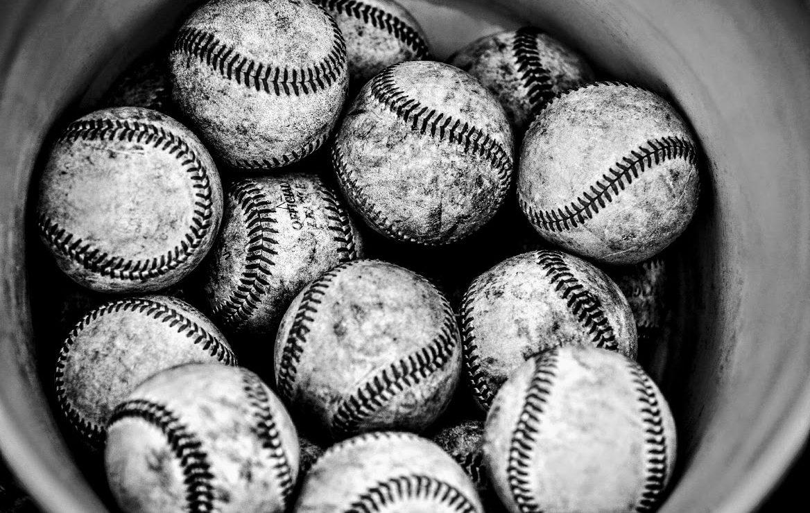 a dozen baseballs in a bucket
