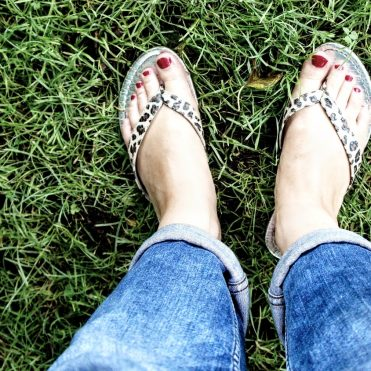 Woman's bare feet with red toenails in flipflops.