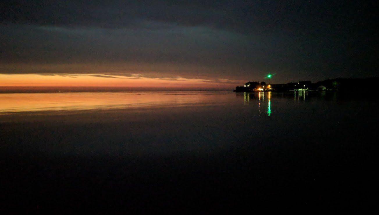 dark ocean at night with band of orange light on horizon