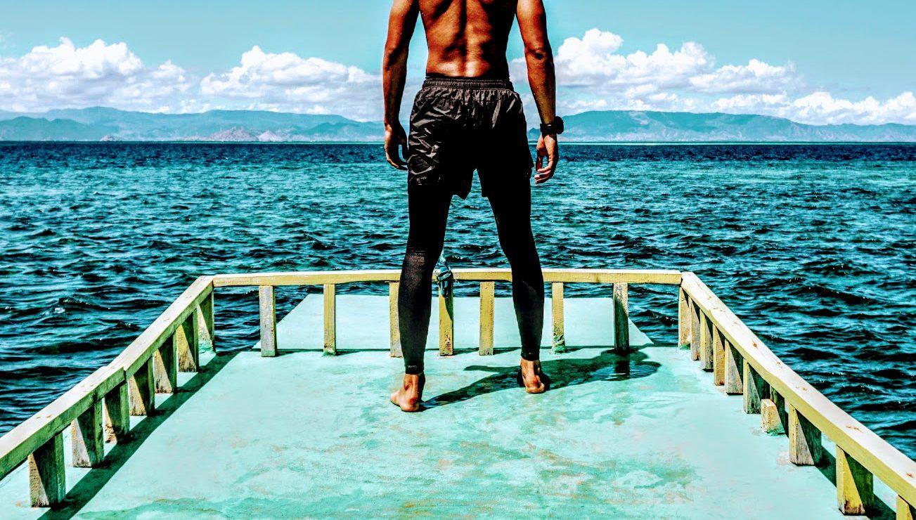 man on dock facing the ocean