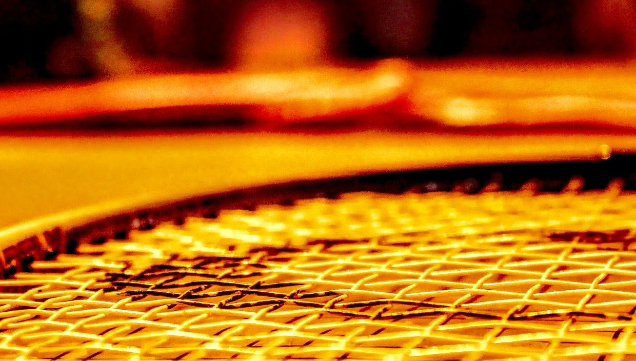 close up of tennis racket strings