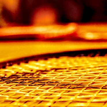 close up of tennis racket strings