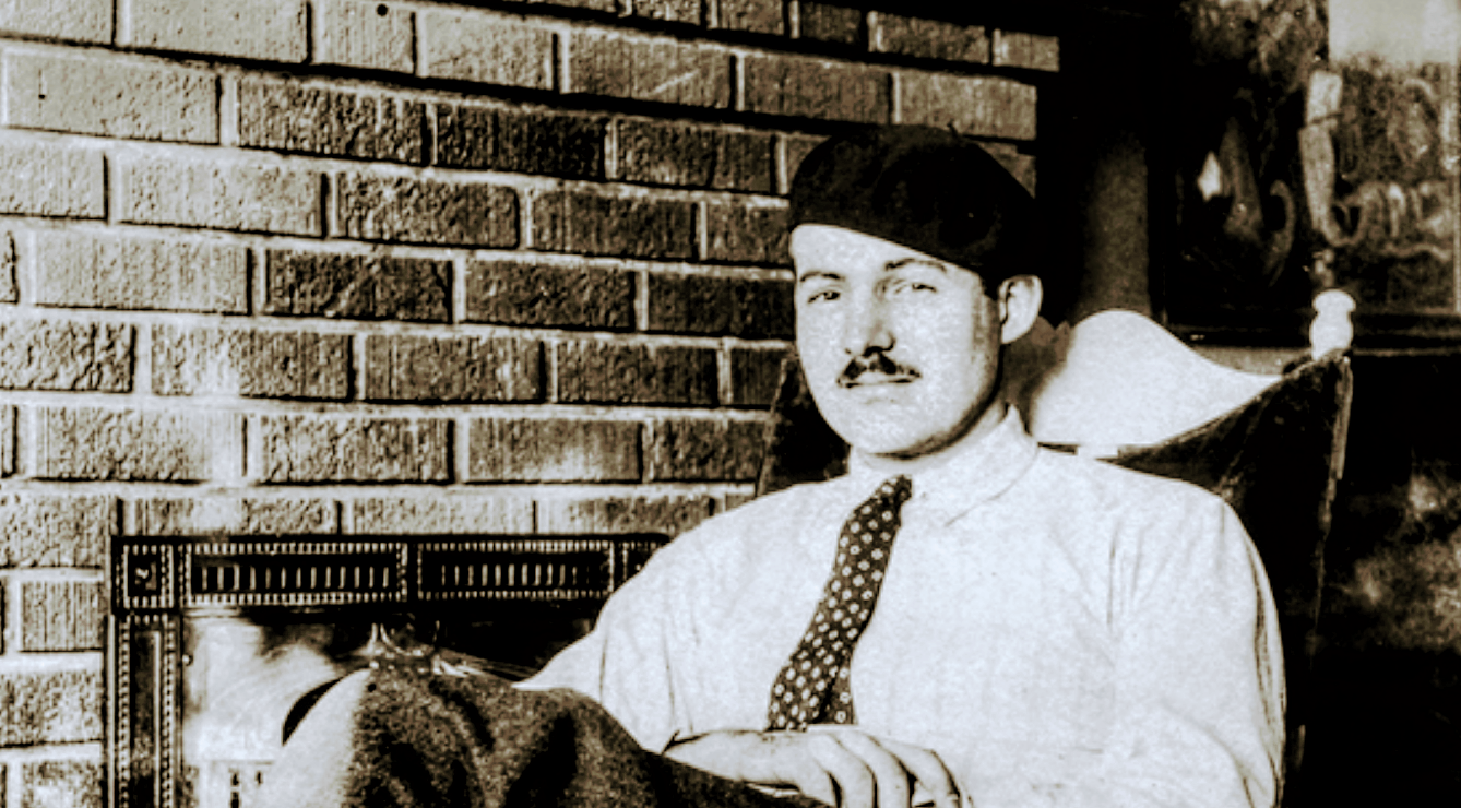 Hemingway sitting in front of a fireplace
