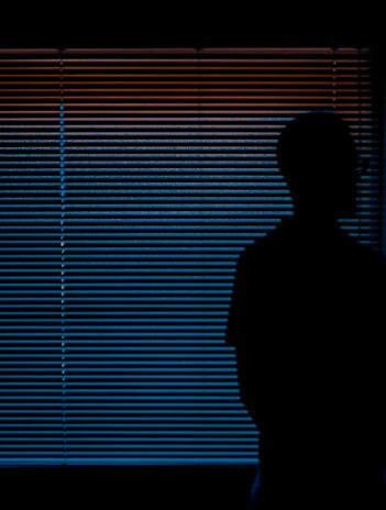 man in dark room with light leaking through window blinds