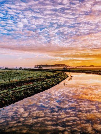 canal under a pink orange sky.