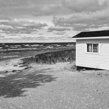 lonely hut on sandy beach with whitecap waves
